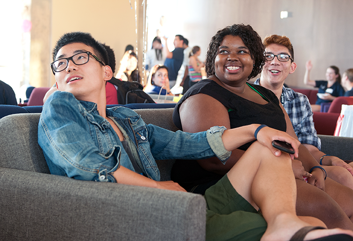Three students sit in a sofa, smiling