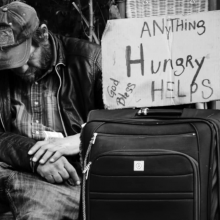 "Homeless man with ""Hungry, Anything Helps, God Bless"" sign"