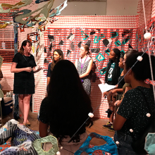 An artist discusses her textile art with members of the Four Year Houses